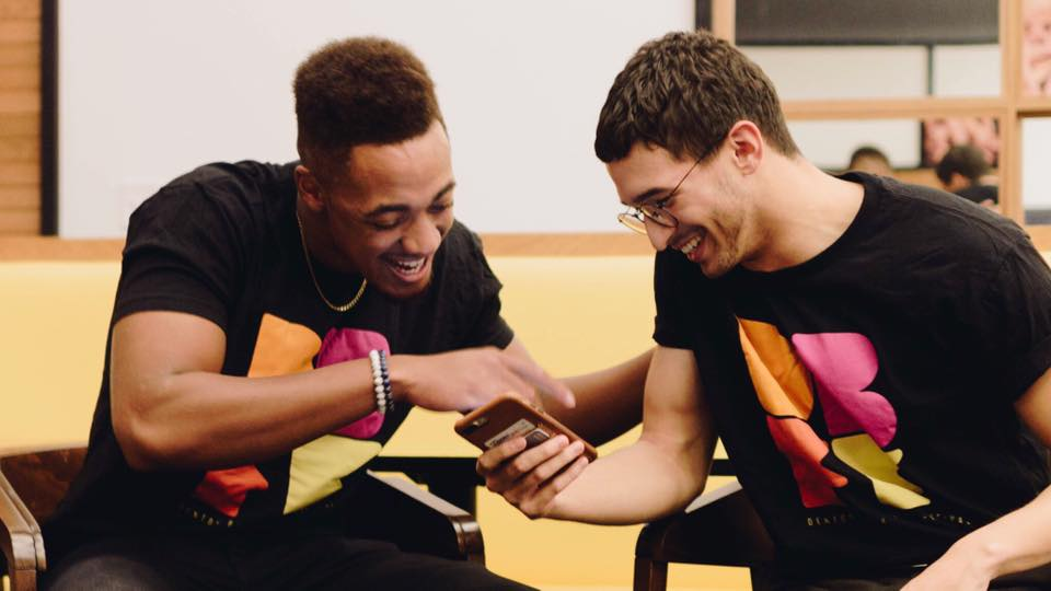 Two young men laugh while talking about something on their smartphones.