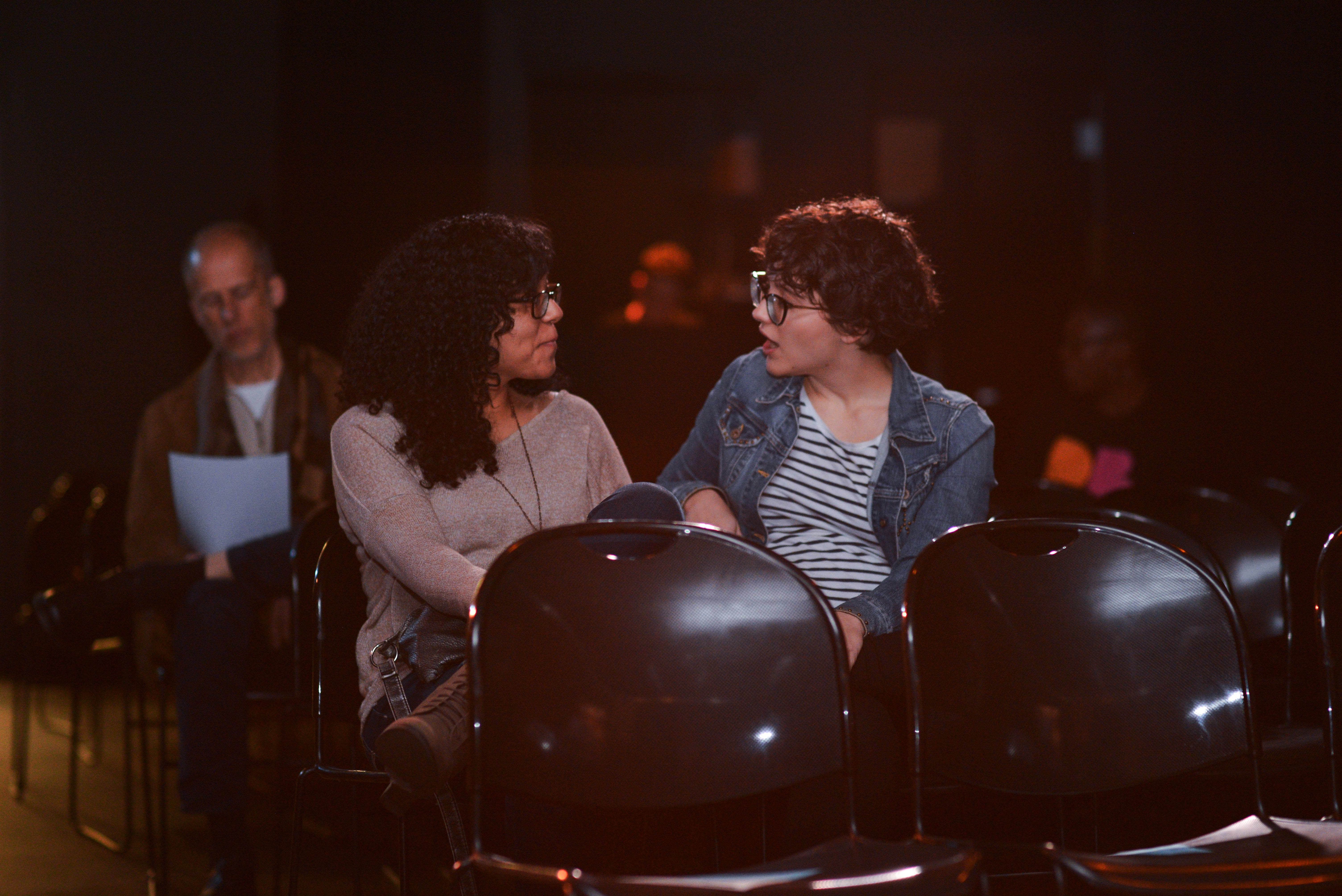 Two women seated together and talking in the Black Box Theatre in Denton, Texas.