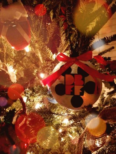 Christmas tree ornament made to look like a film reel with the Denton Black Film Festival logo superimposed on top.