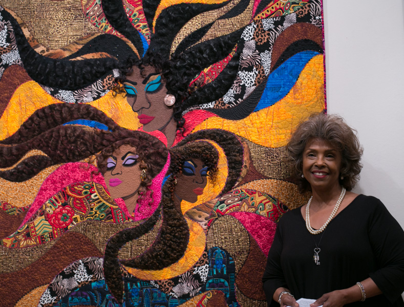 Master Quilter Barbara McCraw stands her to her quilt, Lessie Rose.