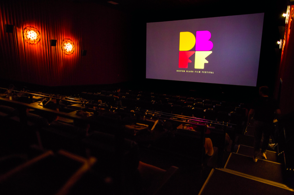 Inside of a dark Alamo Drafthouse theatre with the DBFF logo on the screen