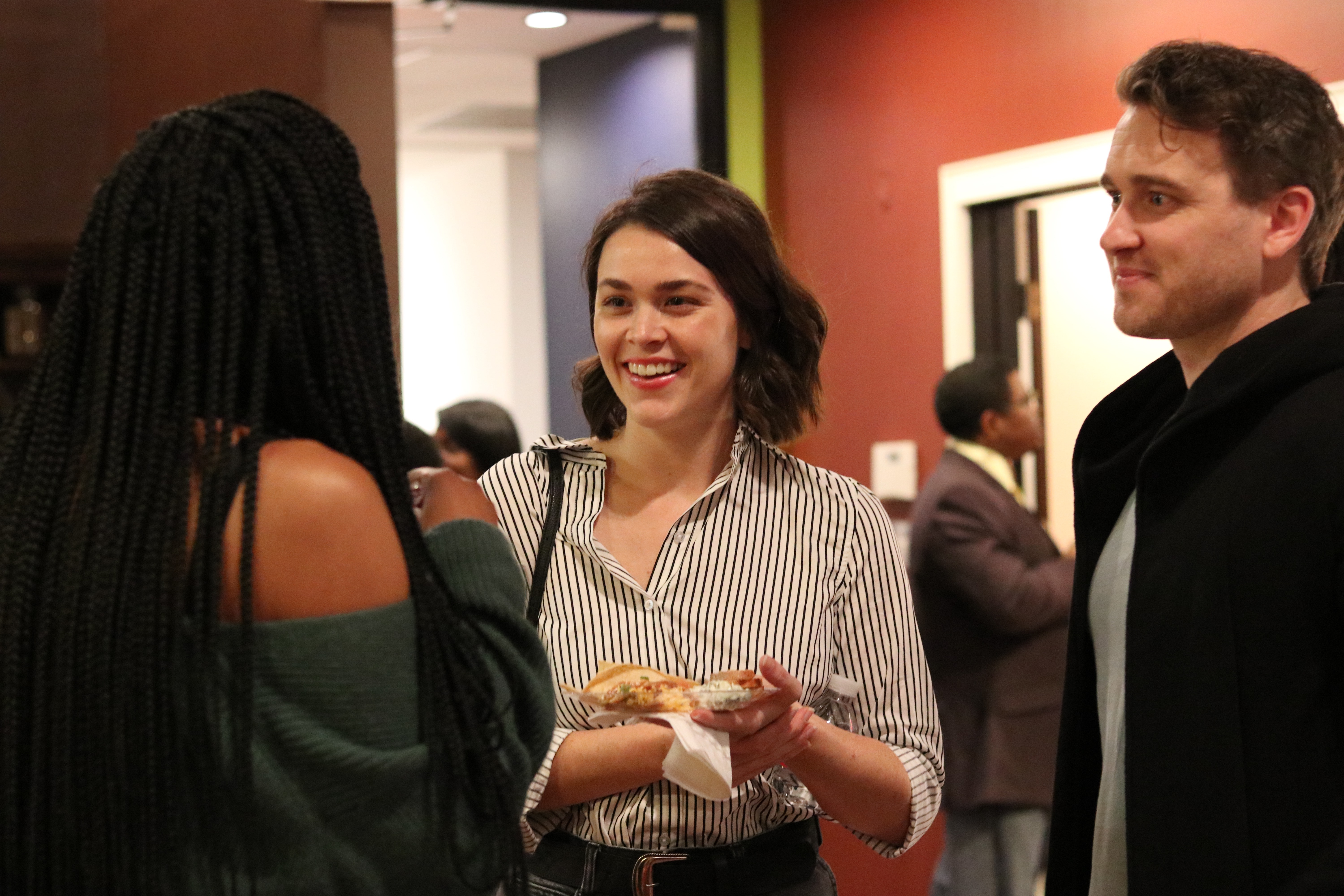 Three creatives/filmmakers talking at a DBFF filmmaker mixer. Two women ane one man are pictured.